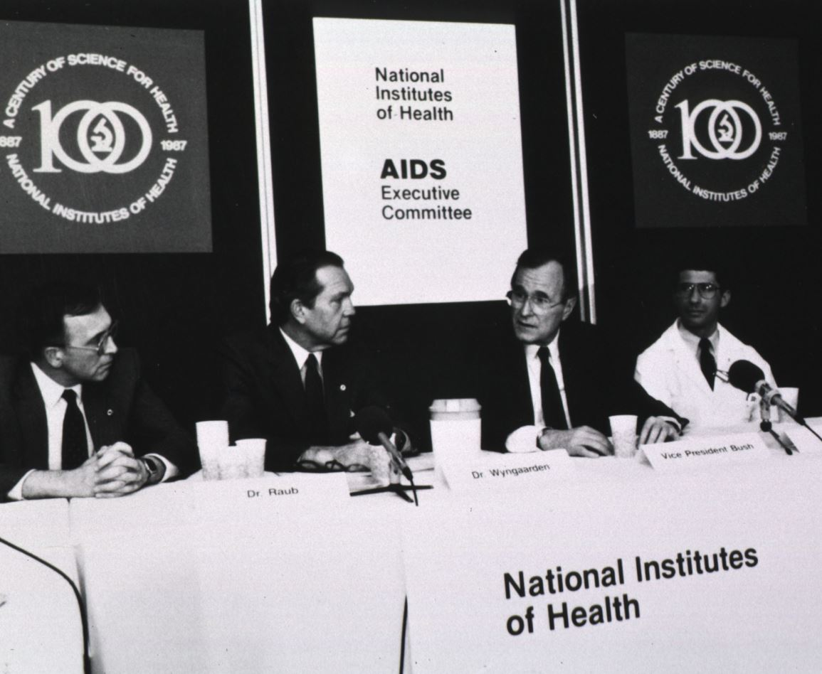 NIH AIDS Executive Committee Meeting, 1980s. From left, Dr. William Raub, then-NIH Director Dr. James Wyngaarden, Vice President George H. W. Bush, and Dr. Anthony Fauci.