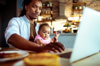 Man working on his laptop at breakfast, with his baby on his lap.